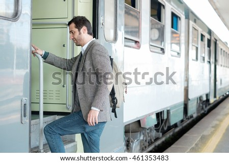 standing man leaving on the train in a train station platform