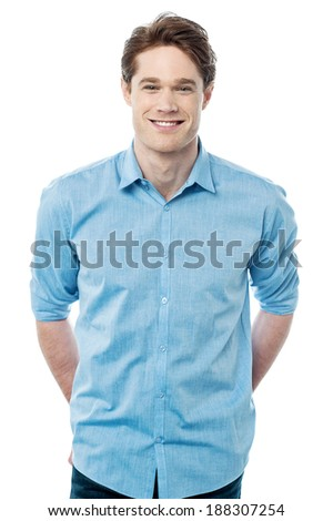 Standing man smiling with hands behind his back  - stock photo