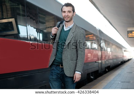 standing man waiting for the train in a train station platform - stock photo