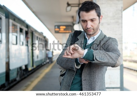 standing man waiting for the train in a train station platform