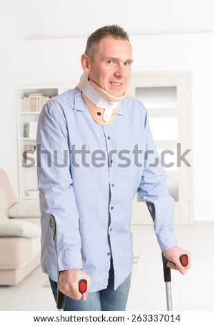 Standing man with crutches and cervical collar - stock photo