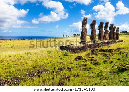Standing moais looking at sea in Easter Island on sunny day - stock photo