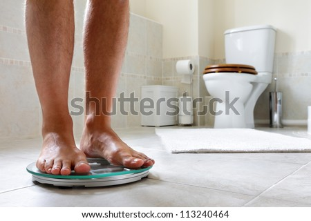 Standing on bathroom scale concept for dieting, slimming or overweight - stock photo