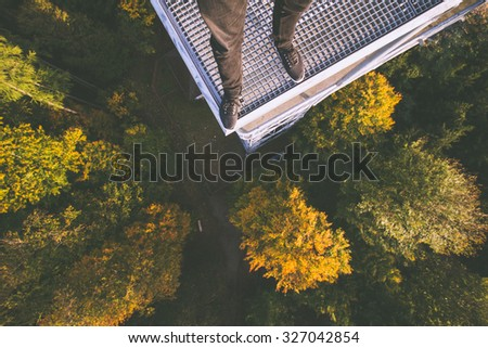 standing on the edge of high tower above forest. - stock photo