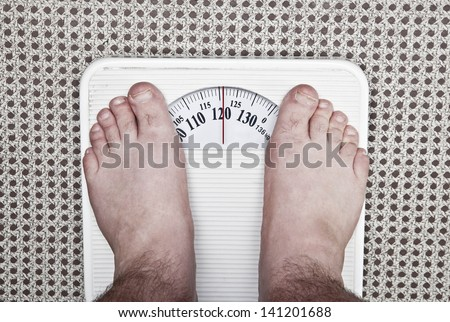 Standing on the weight. Isolated on white background. - stock photo