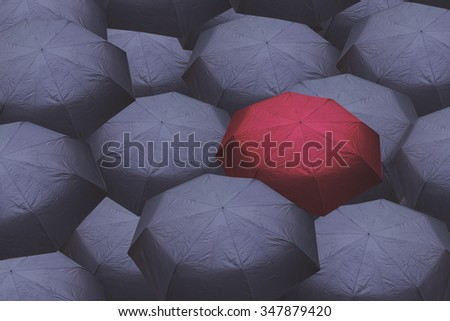 Standing out from the crowd, high angle view of red umbrella over many dark ones - stock photo