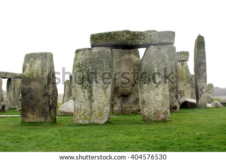 Standing stones of Stonehenge on a lush green lawn, under overcast skies