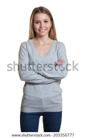 Standing woman in a grey sweater with crossed arms