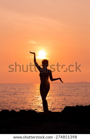 Standing woman silhouette in yoga pose on sunset sea background back lit