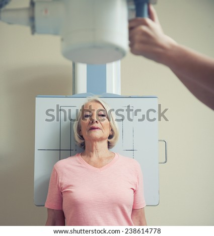 Standing woman undergoing x-ray test. - stock photo