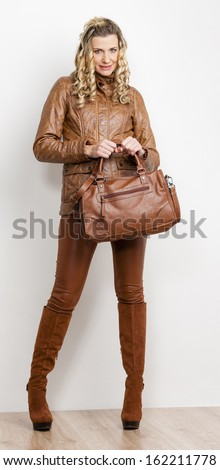 standing woman wearing fashionable brown clothes and boots with a handbag - stock photo