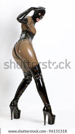 standing woman wearing latex clothes - stock photo