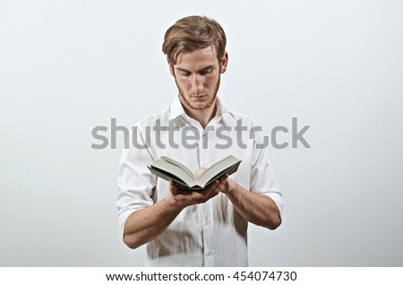 Standing Young Adult Man in White Shirt Keeps a Book in His Hands, Reading - stock photo