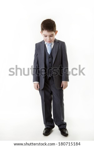 standing young boy dressed up as a business person in a suit looking very unhappy