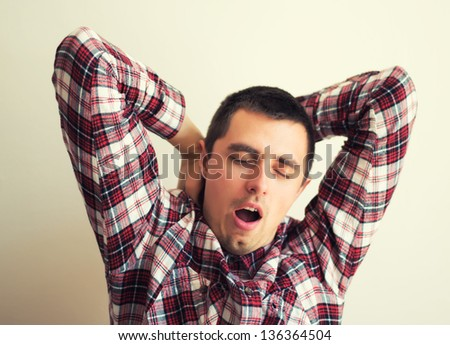 standing young tired man yawning and stretching - stock photo