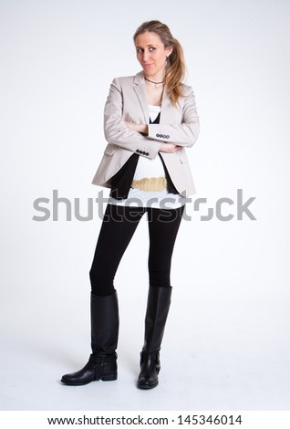 Standing young woman in vest and boots - stock photo