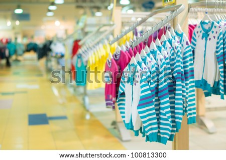 Stands with clothes in kids mall - stock photo