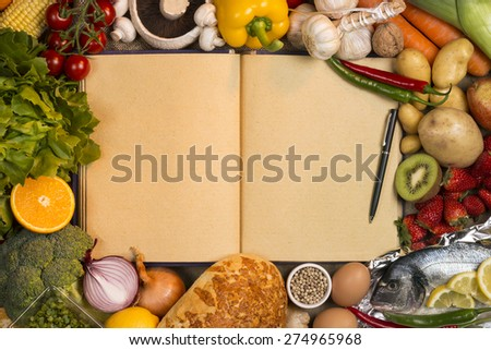 Staple foods - Fruit, Fish, Bread and Vegetables with the blank pages of a recipe book - Space for text. - stock photo