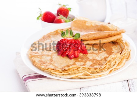 Staple of wheat golden yeast pancakes or crepes, with fresh strawberry on a wooden table on a white background closeup - stock photo