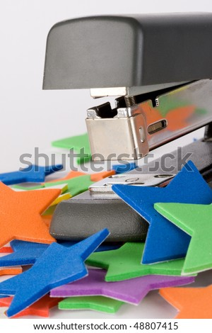 Stapler and color stars isolated on a white background