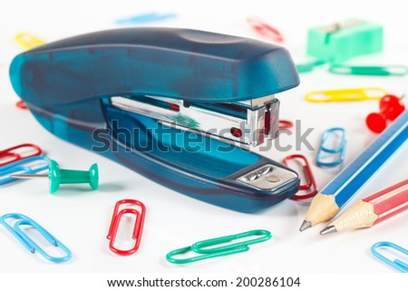 Stapler and multicolored stationery supplies on white desktop close up - stock photo
