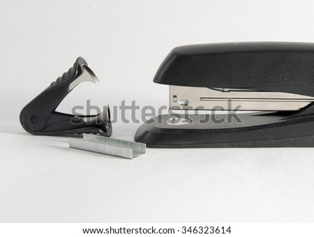 Stapler, staple remover and staples against a white background