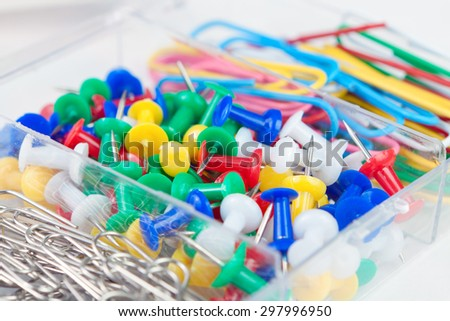 staples and stationery buttons lie in a box for office details - stock photo