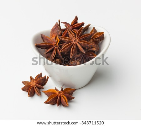 Star anise in a white bowl isolated - stock photo