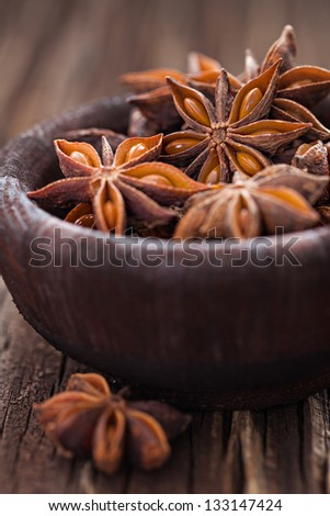 star anise in brown bowl - stock photo