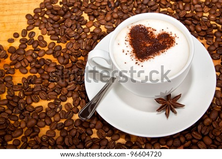 Star aniseed and cacao heart in coffee with coffee beans around it