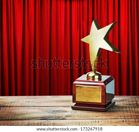 Star award wooden table and on the background of red curtain   - stock photo
