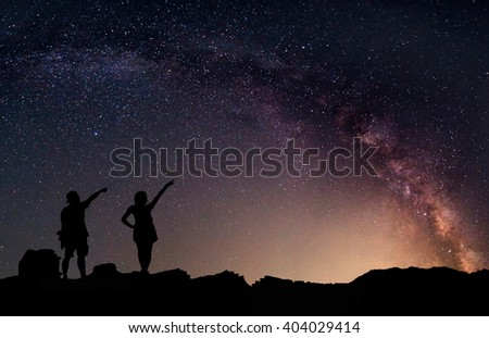 Star-catcher. A person is standing next to the Milky Way galaxy. Elements of this image furnished by NASA. - stock photo