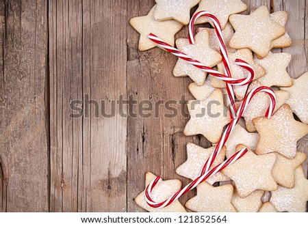 Star Christmas cookies and candy canes framed on wooden background