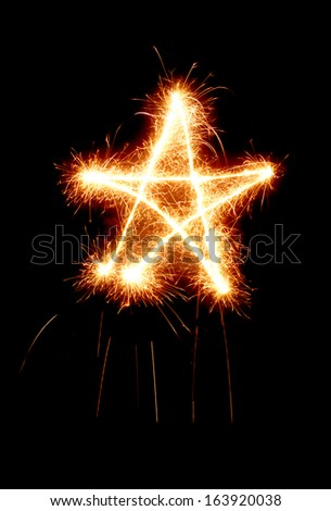 Star made by sparkler isolated on black background. Christmas, holiday, celebration symbol. - stock photo