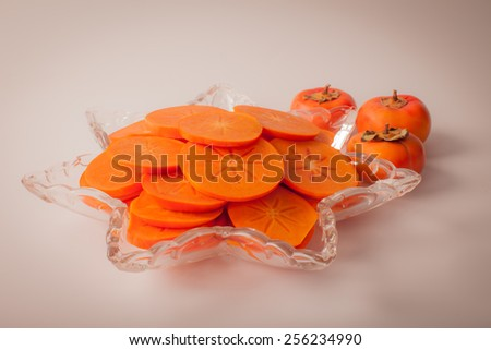 Star platter with sliced persimmons - macro shot - stock photo