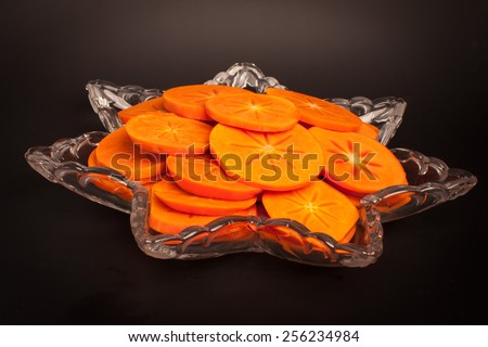 Star platter with sliced persimmons - side view on black background - stock photo
