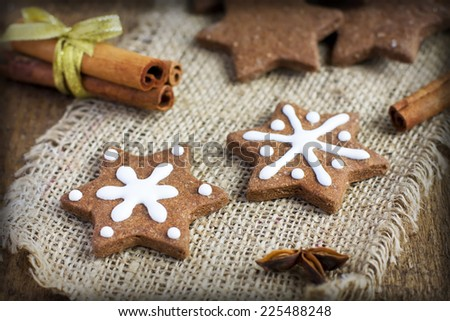 Star shape Christmas chocolate gingerbread Cookie with icing and cinnamon on sacking, toned - stock photo