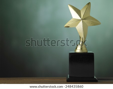 star shape trophy on the green  background - stock photo