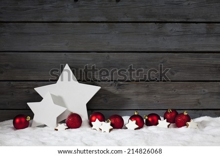 Star shaped christmas decoration christmas bulbs cinnamon stars on pile of snow against wooden wall - stock photo
