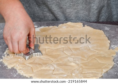 Star Shaped Cookie Cutter Making Christmas Cookies - stock photo