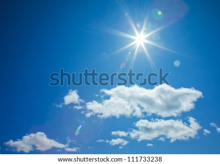 star-shaped sun in blue sky with light clouds - stock photo