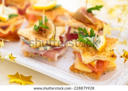 Star shaped toasts with smoked salmon, meat  and cheese.  - stock photo