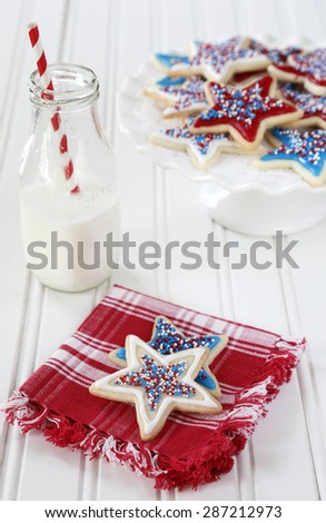 Star sugar cookies decorated for fourth of July celebration. Milk bottle with paper straw.