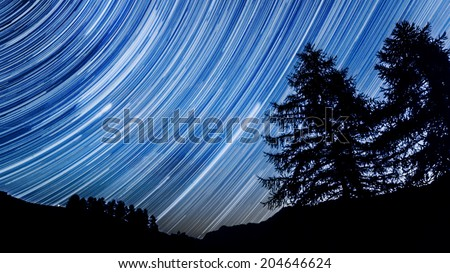 Star trail effect over mountain and trees in night sky  - stock photo
