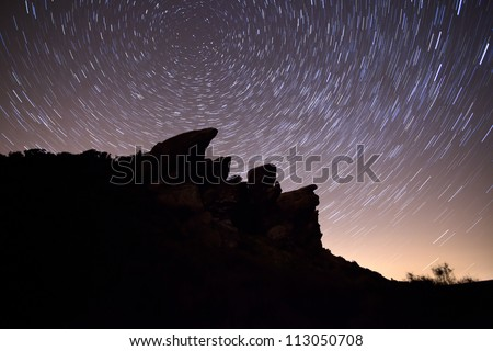 star trails against silhouettes of rocks in the roaches, england