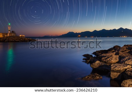 Star Trails at the Harbour with a Lighthouse and Rocks on the Foreground - stock photo
