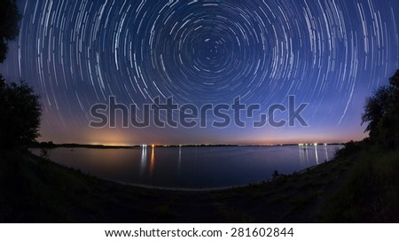 Star trails at the lake side - stock photo