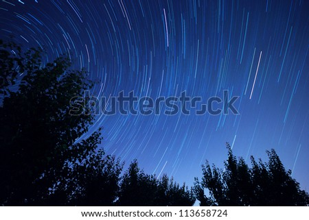 Star trails in the night sky - stock photo