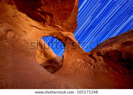 Star Trails Through an Arch in the Desert - stock photo