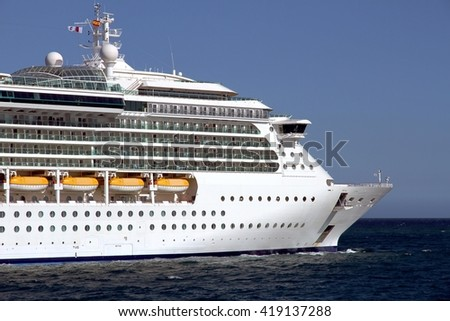 Starboard side of a luxury cruise leaving port.